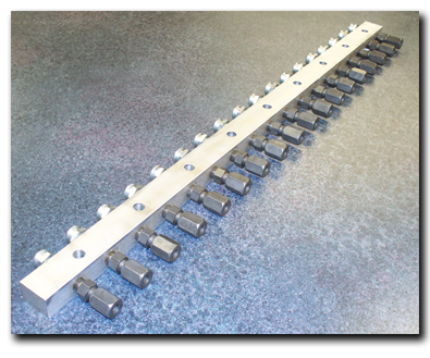 A fully assembled centralized lubrication aluminum manifold equipped with button-style zerks.